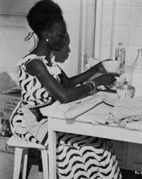 Diouana, dressed for a 'glamorous' life in France, but spending her time in the kitchen
