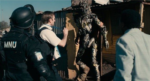 Wickus Van der Merwe from MNU attempts to persuade an alien to sign his eviction notice from District 9