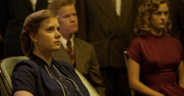 Amy Adams as Peggy Dodd listening to her husband Lancaster giving a presentation.