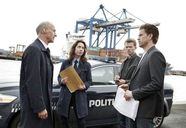 Sofie Gråbøl as Sarah Lund in uniform, with her hair down, at the beginning of The Killing III with (on the right) Sigurd Holmen le Dous and Nikolai Lie Kaas as   Asbjørn Juncker and Mathias Borch. On the left is Stig Hoffmeyer as Niels Reinhardt, one of the major characters in the story.