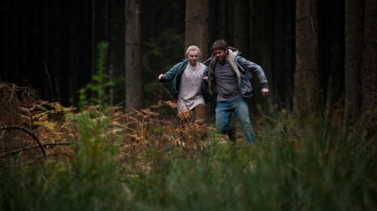 Adele and Timo escape through the woods.