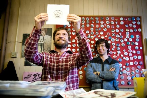 Terri Hooley (Richard Dormer) celebrates a Good Vibrations record release in the shop with Dave Hyndman (Michael Colgan). Hank Williams looks down benignly.