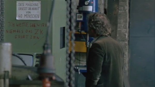 """Klaus in the machine shop where his stepfather works. The sign says """"This machine does the work of 40 men"""". The added graffiti says """"Bet it won't replace the Central Committee [of the Party]"""""""