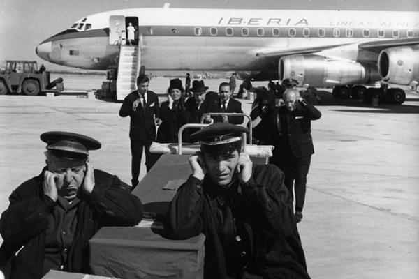 José Luis (Nino Manfredi, on the right in the foreground) tries to block out the noise of the jets when he and his partner collect a coffin from a flight from the US.