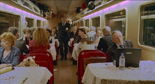 The 'open plan' dining car in the first story. The professor is front right. (Image from DVDBeaver.com)
