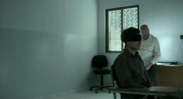 Gael Garcia Bernal as Maziar Bahari (with the blindfold) and Kim Bodnia as the interrogator.