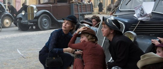 Madame Angellier (Kristin Scott Thomas) and Lucile (Michelle Williams) with the other women as a German aircraft drops propaganda leaflets.
