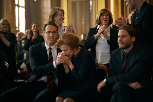 Randy (Ryan Reynolds) attempts to comfort Maria (Helen Mirren) alongside Humbertos (Daniel Bruhl). at oneof many court/tribunal hearings.