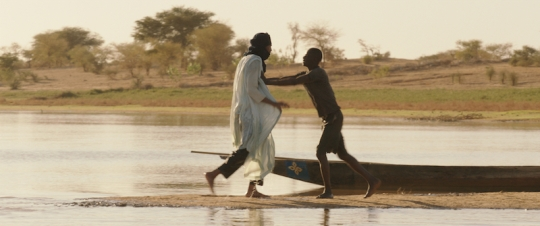 Kidane (Ibrahim Ahmed, left) the herdsman tussles with the fisherman Amadou who has killed one of his cows.