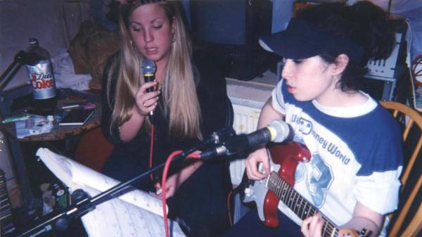A young Amy Winehouse (right) plays guitar in one of the 'found footage' clips