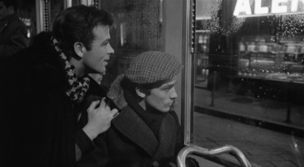 Simone (Renato Salvatori) and Rocco (Alain Delon) get their first glimpse of the lights of Milan through the window of the bus that takes them from the station at the start of the film. (A screengrab from the MOC DVD on the DVD Beaver website.)