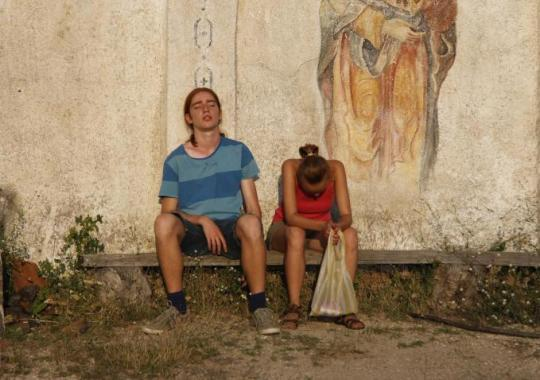The boy and the girl rest outside an abandoned church.