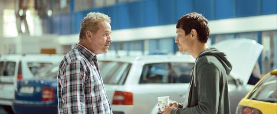 Sandu Patrescu (Theodor Corban, left) confronts his neighbour (Iulian Postelnicu) who has commissioned him to undertake a seemingly meaningless change of vehicle registration.