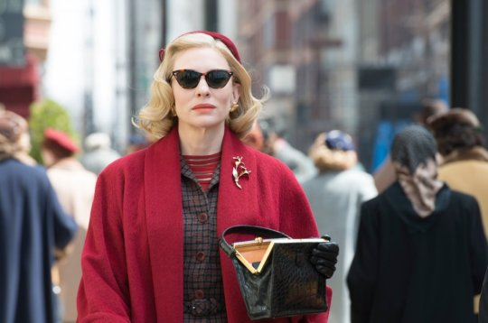Cate Blanchett in a street scene in which her red coat dominates