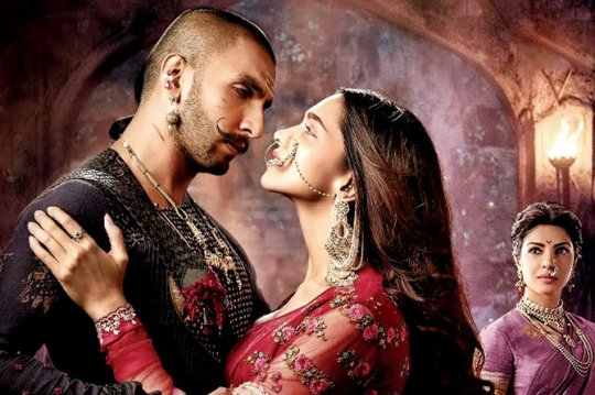 Mastani (Deepika Padukone) and Bajirao (Ranveer Singh) in the foreground, Kashibai (Proyinka Chopra) looks on.