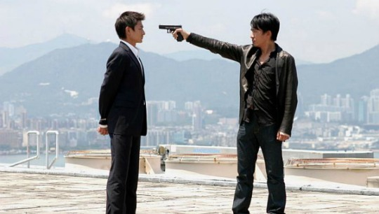 Andy Lau threatened by Tony Leung in an iconic scene from Inernal Affairs, one of the films in CRIME: Hong Kong Style