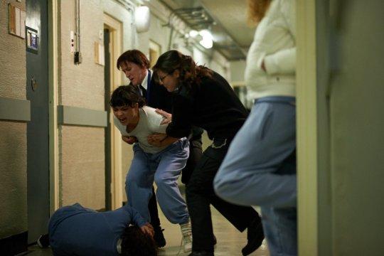 prison warders control Leanne (Isabella Laughland)