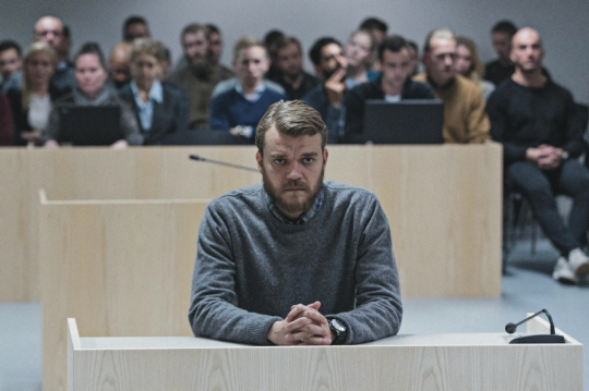 Pilou Asbæk as Claus Pedersen facing lay assessors at the tribunal (with his men behind him in the gallery)