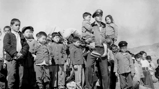 Production still of Rock Hudson with Korean orphans flown to the US for the shoot.