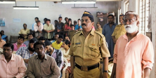 The accused, Narayan Kamble (Vira Sathidir, right) waits in the lower court in which he will be arraigned to appear in the Sessions Court.