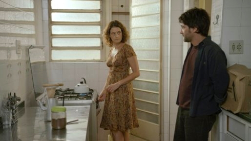 Vera (Denise Varga) in her new kitchen with her mysterious visitor (César Troncoso)