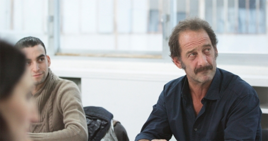 Vincent Lindon as Thierry. In this scene we see him listening to feedback on his performance in a role-play.