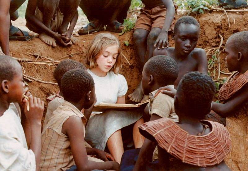 Regina as a young girl (Lea Kurka) reads a story to the village children