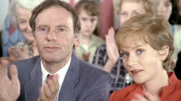 Vic (Jean-Louis Trintignant) and Mélanie (Isabelle Hupert) watch their daughter at a piano recital at school