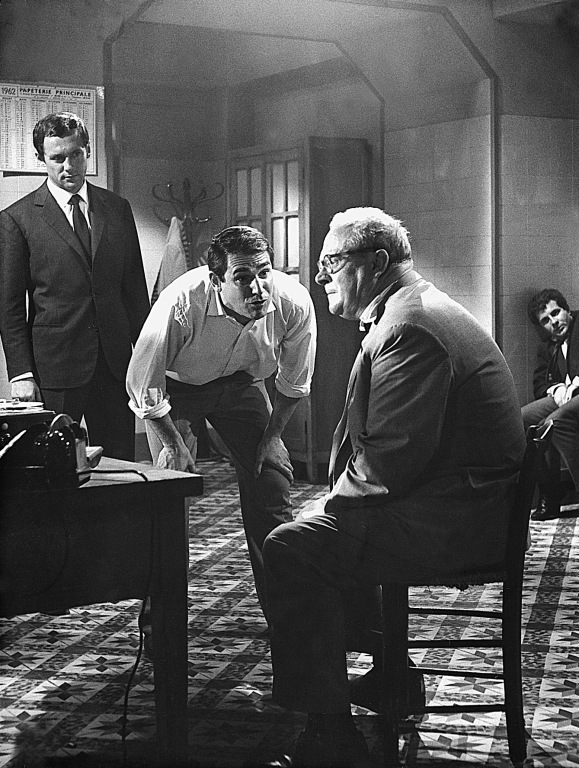 Interrogation by the detective Corbi (Robert Hossein) of Kimmel (Gert Froebe). Ronet is behind left and in the far background is Harry Meyen as Toni (a witness)