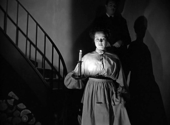 Elsa Lanchester as Mrs Sloane descends the stairs to the basement with George Brent as Professor Warren behind.